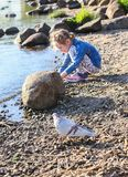Adorable little girl playing with small stones on the river coast at spring. stock images