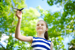 Adorable little girl playing with small toy airplane outdoors Stock Photography