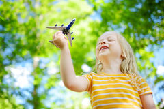 Adorable little girl playing with small toy airplane outdoors Royalty Free Stock Images