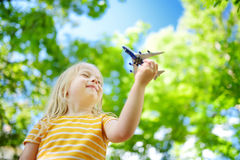 Adorable little girl playing with small toy airplane outdoors Stock Photos
