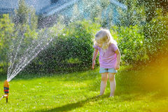 Adorable little girl playing with a sprinkler Royalty Free Stock Photos