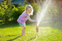 Adorable little girl playing with a sprinkler Royalty Free Stock Photography