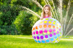 Adorable little girl playing with a sprinkler in a backyard on sunny summer day. Cute child having fun with water outdoors. Stock Photos