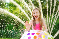 Adorable little girl playing with a sprinkler in a backyard on sunny summer day. Cute child having fun with water outdoors. Royalty Free Stock Photography