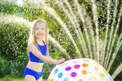Adorable little girl playing with a sprinkler in a backyard on sunny summer day. Cute child having fun with water outdoors. Royalty Free Stock Photos