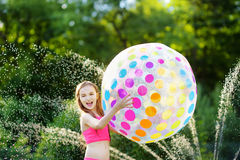 Adorable little girl playing with a sprinkler in a backyard on sunny summer day. Cute child having fun with water outdoors. Royalty Free Stock Images