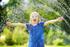 Adorable little girl playing with a sprinkler in a backyard on sunny summer day. Cute child having fun with water outdoors. Royalty Free Stock Photo