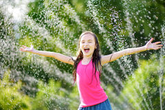 Adorable little girl playing with a sprinkler in a backyard on sunny summer day. Cute child having fun with water outdoors. Stock Image
