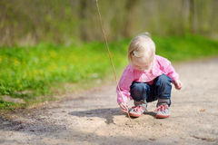 Adorable little girl playing with a stick Royalty Free Stock Photos