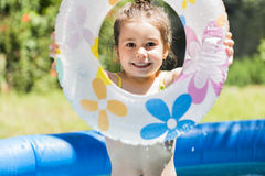 Adorable little girl playing at a swimming pool Royalty Free Stock Images