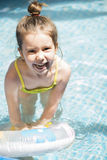Adorable little girl playing at a swimming pool Stock Photo