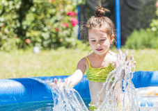 Adorable little girl playing at a swimming pool Stock Images