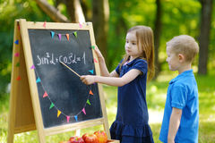 Adorable little girl playing a teacher Stock Photo