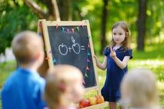 Adorable little girl playing a teacher Stock Photo