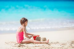 Adorable little girl playing with beach toys on white tropial beach Royalty Free Stock Photos