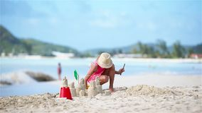 Adorable little girl playing with toys on beach vacation. Kid making a sand castle on the seashore stock footage