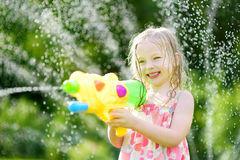 Adorable little girl playing with water gun on hot summer day. Cute child having fun with water outdoors. Stock Photos