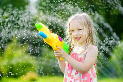 Adorable little girl playing with water gun on hot summer day. Cute child having fun with water outdoors. Funny summer games for kids royalty free stock photo