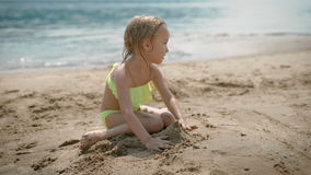 Adorable little girl playing on white sand beach. Adorable little blonde girl playing on white sand beach stock video footage