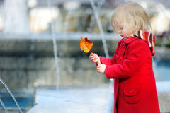 Adorable little girl playing with yellow autumn leaf Stock Photo