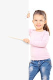Adorable little girl pointing to a blank panel with stick Stock Images