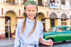 Adorable little girl in popular area in Old Havana, Cuba. Portrait of kid background vintage classic american car royalty free stock photos