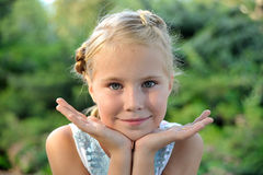 Adorable little girl portrait. Adorable little blonde girl portrait with hands outdoor Royalty Free Stock Image