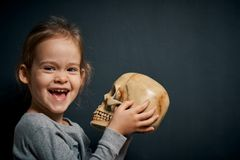 Adorable little girl poses with a skull. On a black background stock photo
