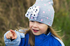 Adorable little girl posing on blurred background and smiling in. To a camera. Wearing winter coat and hat. Lovely young girl in the autumn outdoors Stock Photography