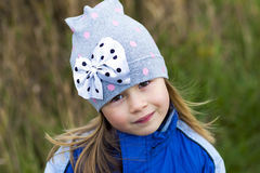 Adorable little girl posing on blurred background and smiling in. To a camera. Wearing winter coat and hat. Lovely young girl in the autumn outdoors Royalty Free Stock Photography