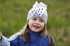 Adorable little girl posing on blurred background and smiling in. To a camera. Wearing winter coat and hat. Lovely young girl in the autumn outdoors Stock Photo