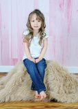 Adorable little girl posing on brown fur rug Royalty Free Stock Image