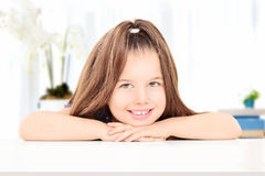 Adorable little girl posing seated at a table Royalty Free Stock Images