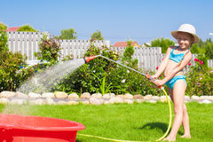 Adorable little girl pouring water from hose and Stock Photography