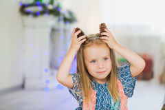 Adorable little girl pretending to be dog pinecones as puppy ears. Adorable little girl pretending to be dogs pinecones as puppy ears. Smiling child on christmas Royalty Free Stock Photography