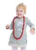 Adorable little girl put on her big red beads Stock Photography