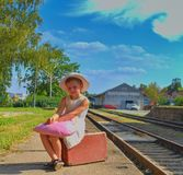 Adorable little girl on a railway station, waiting for the train with vintage suitcase. Traveling, holiday and chilhood stock photo