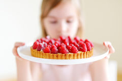 Adorable little girl and a raspberry cake Royalty Free Stock Photos