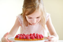 Adorable little girl and a raspberry cake Royalty Free Stock Images