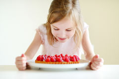 Adorable little girl and raspbrerry cake Royalty Free Stock Photo