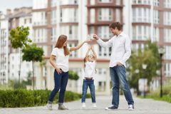 Happy family in front of new apartment building. Adorable little girl reaching to the keys her parents are holding. Family posing outdoors in front of a modern Royalty Free Stock Images
