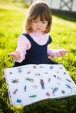 Adorable little girl reading book a stock photos