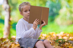 Adorable little girl reading a book in beautiful Stock Photography