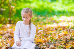 Adorable little girl reading a book in beautiful Royalty Free Stock Photos