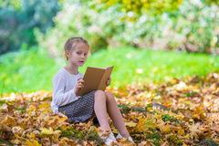 Adorable little girl reading a book in beautiful Stock Images