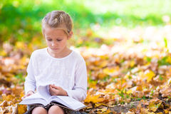 Adorable little girl reading a book in beautiful Royalty Free Stock Images