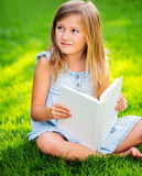 Adorable little girl reading book Stock Images