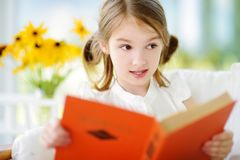 Adorable little girl reading a book in white living room Stock Photos