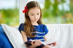 Adorable little girl reading a book in white living room on beautiful summer day. Royalty Free Stock Photography