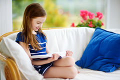 Adorable little girl reading a book in white living room on beautiful summer day Stock Images